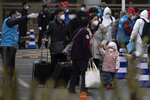 Returnees from the Hubei Province are directed by volunteers to buses waiting to disperse them to their homes upon arriving at the West Train Station in Beijing on Thursday, March 26, 2020. China is allowing people who were under lockdown in Hubei to leave the province at the center of the coronavirus outbreak now sweeping the globe. In the nation's capital, authorities are accepting about 800 people a day from Hubei. (AP Photo/Ng Han Guan)