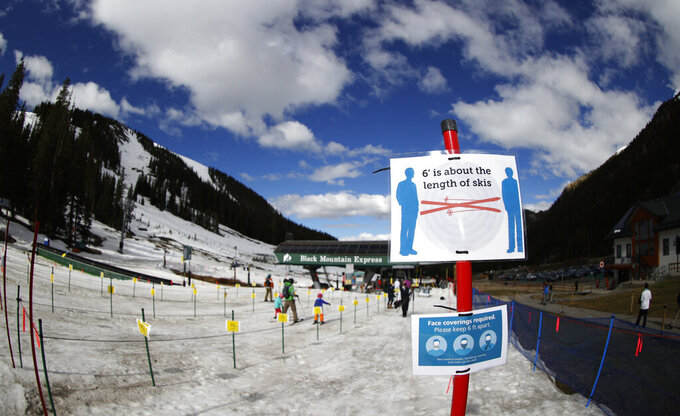 Signs stand at the lines to the lift at the reopening of Arapahoe Basin Ski Resort, which closed in mid-March to help in the effort to stop the spread of the new coronavirus, Wednesday, May 27, 2020, in Keystone, Colo. The ski area is the only one in the state to take advantage of the relaxation of coronavirus restrictions by Colorado. (AP Photo/David Zalubowski)