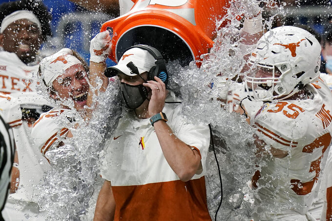 Texas coach Tom Herman, center, is doused by players as they celebrate a win over Colorado in the Alamo Bowl NCAA college football game Tuesday, Dec. 29, 2020, in San Antonio. (AP Photo/Eric Gay)