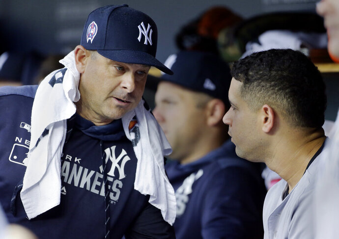 New York Yankees manager Aaron Boone, left, talks with catcher Gary Sanchez during the second inning of the second game of a baseball doubleheader against the Detroit Tigers, Thursday, Sept. 12, 2019, in Detroit. (AP Photo/Duane Burleson)