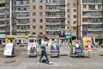 A man walks past election stands of various parties including ruling Mongolian People's Party and independent candidates in the Songinokhairkhan district on the outskirts of Ulaanbaatar, Mongolia, Monday, June 22, 2020. Mongolia holds parliamentary elections on Wednesday, continuing a nearly 30-year democratic system in a vast but lightly populated country sandwiched between authoritarian regimes in Russia and China and beset by economic problems. (AP Photo/Ganbat Namjilsangarav)