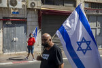 Supporters of Prime Minister Benjamin Netanyahu wave flags outside the district court in Jerusalem, Sunday, July 19, 2020. The corruption trial of Netanyahu has resumed following a two-month hiatus. (AP Photo/Ariel Schalit)