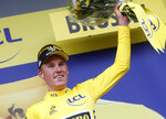 Netherlands' Mike Teunissen wearing the overall leader's yellow jersey celebrates on the podium after winning the first stage of the Tour de France cycling race over 194.5 kilometers (120,86 miles) with start in Brussels and finish in Brussels. Saturday, July 6, 2019. (AP Photo/Thibault Camus)