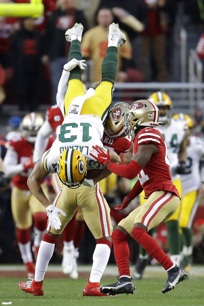 Green Bay Packers wide receiver Allen Lazard (13) is tackled by San Francisco 49ers free safety Jimmie Ward, obscured, as Emmanuel Moseley watches next tduring the first half of the NFL NFC Championship football game Sunday, Jan. 19, 2020, in Santa Clara, Calif. (AP Photo/Ben Margot)