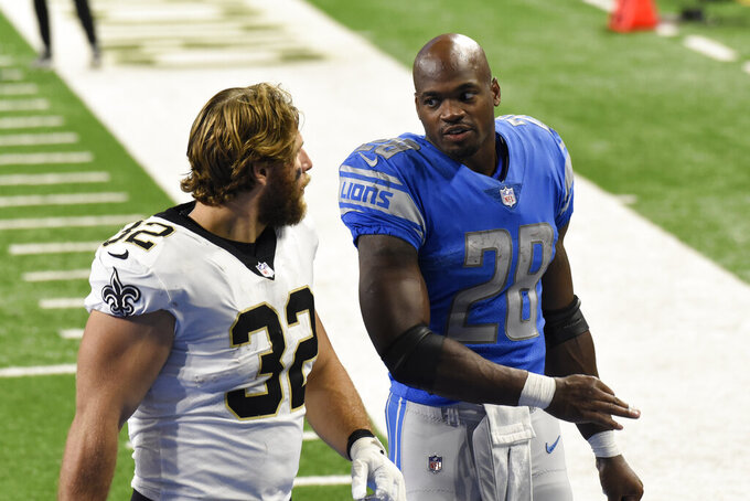 New Orleans Saints running back Michael Burton (32) and Detroit Lions running back Adrian Peterson (28) walk off the field after an NFL football game, Sunday, Oct. 4, 2020, in Detroit. (AP Photo/Jose Juarez)
