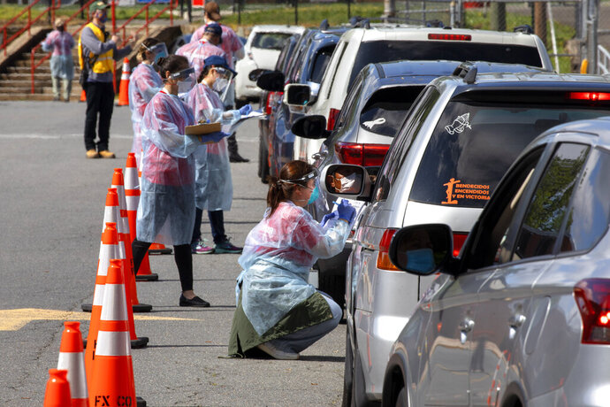 FILE - In this Saturday, May 23, 2020, file photo, a man wearing a face mask is reflected in a mirror as he waits inside his car to be tested for COVID-19 while volunteers take registration information in Annandale, Va. COVID-19 testing was available from Fairfax County at no cost and without a doctor's order. Hundreds of people had lined up in cars and on foot by 10 a.m. Officials planned on testing about 1,000 people from 10 a.m. to 6 p.m. (AP Photo/Jacquelyn Martin)