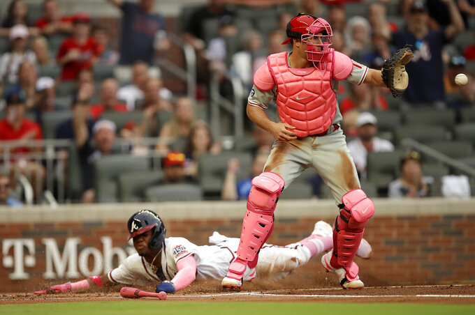 Atlanta Braves' Ronald Acuna Jr. slides safe to score as Philadelphia Phillies catcher J.T. Realmuto waits for the ball in the first inning of a baseball game Sunday, May 9, 2021, in Atlanta. Acuna scored on a single by Braves' Freddie Freeman. (AP Photo/Ben Margot)
