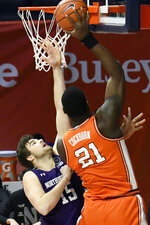 Illinois center Kofi Cockburn (21) puts the ball in as Northwestern's center Ryan Young (15) defends in the first half of an NCAA college basketball game Tuesday, Feb. 16, 2021, in Champaign, Ill. (AP Photo/Holly Hart)