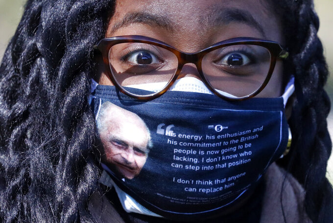 A woman wears a face covering with a picture of the Duke of Edinburgh as he walks along the Long Walk in Windsor, Saturday, April 17, 2021. Britain's Prince Philip, husband of Queen Elizabeth II, died Friday April 9, aged 99, his funeral service takes place at Windsor Castle in St George's Chapel. (AP Photo/Frank Augstein)