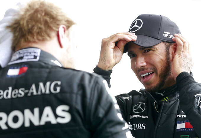 Race winner Mercedes driver Lewis Hamilton of Britain, right, speaks with second placed Mercedes driver Valtteri Bottas of Finland after the Formula One Grand Prix at the Spa-Francorchamps racetrack in Spa, Belgium, Sunday, Aug. 30, 2020. (Stephanie Lecocq, Pool via AP)
