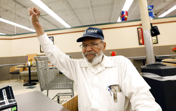 FILE - In this July 19, 2018, file photo, civil rights movement activist James Meredith, right, greets a friend with a black power salute as he takes a coffee break at a north Jackson, Miss., grocery store.