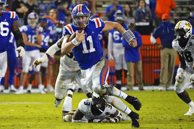 Florida quarterback Kyle Trask (11) runs past Missouri's Martez Manuel (3) and linebacker Nick Bolton, back left, during the second half of an NCAA college football game Saturday, Oct. 31, 2020, in Gainesville, Fla. (AP Photo/John Raoux)