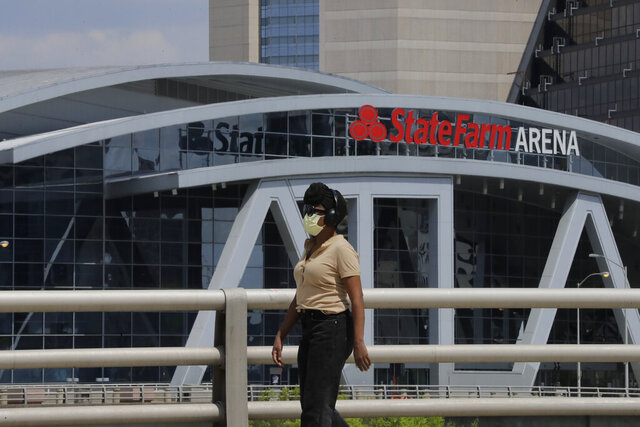 A person wearing a mask walks near the StateFarm Arena where the men's Final Four NCAA college basketball championship game was to be played on Monday, April 6, 2020, in Atlanta. The entire NCAA tournament was canceled due to the COVID-19 virus. (AP Photo/Brynn Anderson)