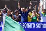 Brazilian President Jair Bolsonaro gestures to supporters, next to his wife Michelle de Paula Firmo Reinaldo Bolsonaro, during Independence Day events in Brasilia, Brazil, Tuesday, Sept. 7, 2021. (AP Photo/Eraldo Peres)