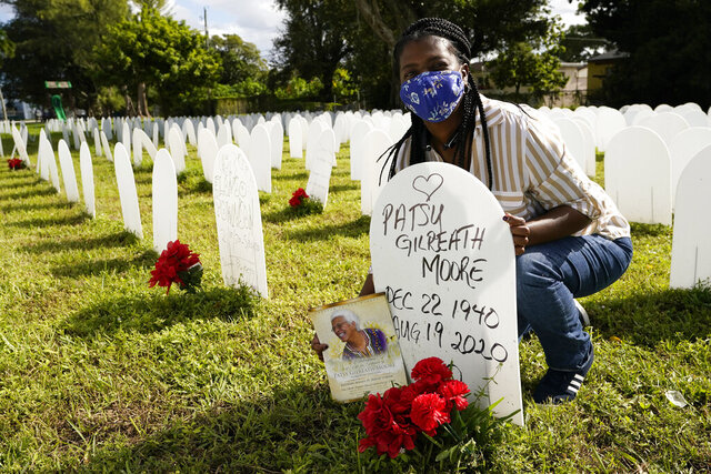 Joana Moore holds a portrait of her mother Patsy Gilreath Moore who died at age 79 from COVID-19 as she poses for a photograph at a symbolic cemetery created to remember and honor lives lost to COVID-19, Tuesday, Nov. 24, 2020, in the Liberty City neighborhood of Miami. Officials announced that a new COVID-19 testing site will be opening in the neighborhood. (AP Photo/Lynne Sladky)