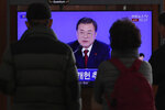 People watch a TV screen showing the live broadcast of South Korean President Moon Jae-in's New Year's press conference at the Seoul Railway Station in Seoul, South Korea, Tuesday, Jan. 14, 2020. (AP Photo/Lee Jin-man)