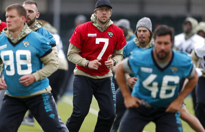 Jaguars QB Nick Foles, centre, warms up with the team during a NFL training session of the Jacksonville Jaguars at the at Allianz Park in London, Friday, Nov. 1, 2019.The Jacksonville Jaguars are preparing for an NFL regular season game against the Houston Texans in London on Sunday. (AP Photo/Frank Augstein)