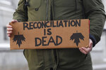 A protester carries a sign as he and others were marching on a street in Ottawa, Ontario, Wednesday, Feb. 12, 2020. The protesters are standing in solidarity with the Wet'suwet'en hereditary chiefs opposed to a Canada gas pipeline in northern British Columbia. (Adrian Wyld/The Canadian Press via AP)