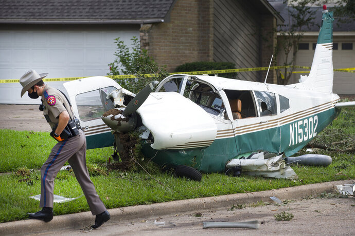 A law enforcement officer works at the site of the crash of a plane, in the front yard of a home Tuesday, July 28, 2020 in Houston. Two people were injured when a single-engine airplane crashed in a residential area early Tuesday, authorities said. The airplane hit a tree and landed in a front yard shortly before 2 a.m. (Brett Coomer/Houston Chronicle via AP)