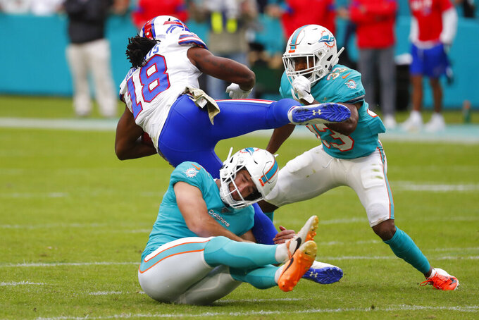 Miami Dolphins kicker Jason Sanders (7) grabs the leg of Buffalo Bills wide receiver Andre Roberts (18) as Miami Dolphins cornerback Jomal Wiltz (33) attempts to tackle, during the second half at an NFL football game, Sunday, Nov. 17, 2019, in Miami Gardens, Fla. (AP Photo/Wilfredo Lee)