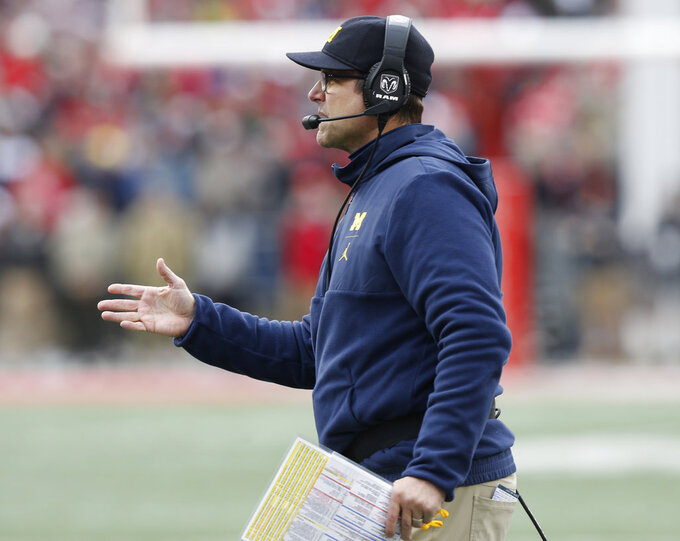 Michigan head coach Jim Harbaugh signals to his team during the second half of an NCAA college football game against Ohio State, Saturday, Nov. 24, 2018, in Columbus, Ohio. Ohio State beat Michigan 62-39. (AP Photo/Jay LaPrete)