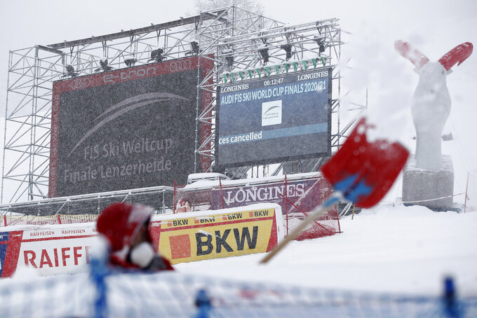 A man is clearing snow in the finish area as the alpine ski, men's and women's World Cup downhill were cancelled due to weather conditions, in Lenzerheide, Switzerland, Wednesday, March 17, 2021. (AP Photo/Gabriele Facciotti)