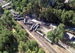 FILE - This June 4, 2016 file photo provided by the Washington State Department of Ecology, shows scattered and burned oil tank cars after a train derailed and burned near Mosier, Ore. The Trump administration is withdrawing a proposal for freight trains to have at least two crew members that was drafted in response to explosions of crude oil trains in the U.S. and Canada. Transportation officials said Thursday, May 23, 2019 that a review of accident data did not support the notion that having one crew member is less safe than a multi-person crew. (Washington Department of Ecology via AP, File)