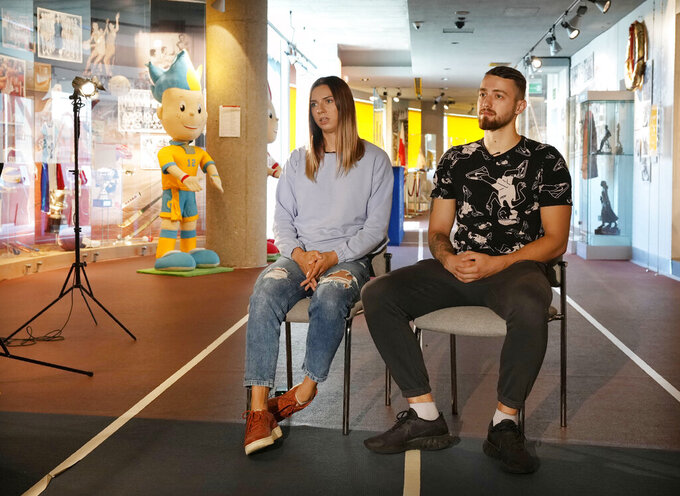 Belarusian Olympic sprinter Krystsina Tsimanouskaya, left, and her husband Arseni Zdanevich speak to The Associated Press in Warsaw, Poland, on Wednesday Aug. 11, 2021. The runner, who has found refuge to rebuild her life in Poland, described the feeling of safety when police took her away from her national team officials. (AP Photo/Czarek Sokolowski)