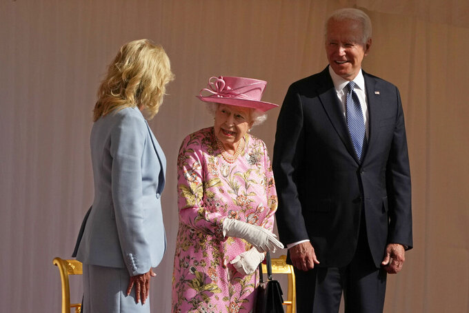 Britain's Queen Elizabeth II speaks to US First Lady Jill Biden, left, while US President Joe Bidenlooks on, while watching a Guard of Honour march past before their meeting at Windsor Castle near London, Sunday, June 13, 2021. (AP Photo/Matt Dunham, Pool)