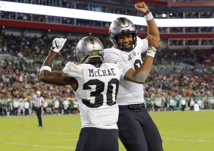 Central Florida's Greg McCrae (30) celebrates with quarterback Darriel Mack Jr. after his third rushing touchdown against South Florida during the second half of an NCAA college football game Friday, Nov. 23, 2018, in Tampa, Fla. (AP Photo/Mike Carlson)