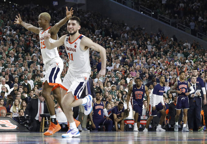 Virginia's Mamadi Diakite, left, and Ty Jerome celebrate at the end of a semifinal round game against Auburn in the Final Four NCAA college basketball tournament, Saturday, April 6, 2019, in Minneapolis. (AP Photo/David J. Phillip)