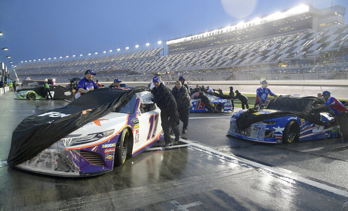 Denny Hamlin's crew pushes his car back to the garage area after the NASCAR Cup Series auto race was postponed because of rain at Daytona International Speedway, Saturday, July 6, 2019, in Daytona Beach, Fla. The race was rescheduled for Sunday. (AP Photo/Phelan Ebenhack)