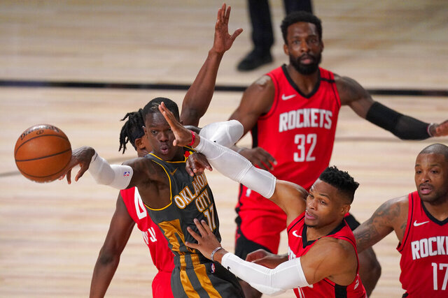 Oklahoma City Thunder's Dennis Schroder (17) is forced to pass the ball as Houston Rockets' Russell Westbrook, bottom center, Jeff Green (32) and P.J. Tucker (17) defend during the second half of an NBA first-round playoff basketball game, Monday, Aug. 31, 2020, in Lake Buena Vista, Fla. (AP Photo/Mark J. Terrill)