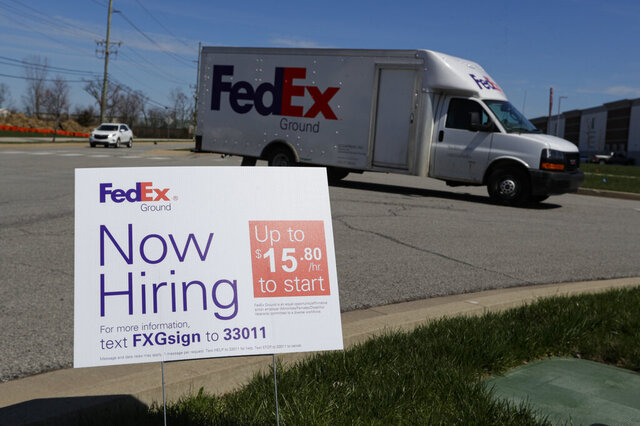 A sign advertising for jobs sits along the roadside outside a FedEx location in Zionsville, Ind., Thursday, April 2, 2020. More than 6.6 million Americans applied for unemployment benefits the week of March 23, far exceeding a record high set just last week, a sign that layoffs are accelerating in the midst of the coronavirus. (AP Photo/Michael Conroy)