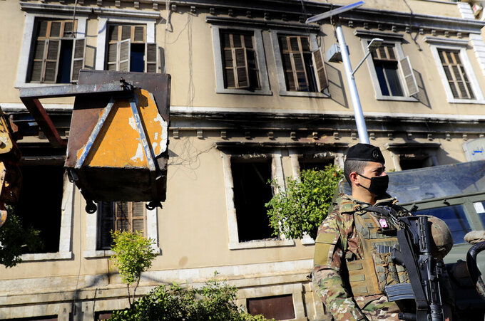 A Lebanese army soldier stand guards outside the building of Tripoli municipality that was set on fire by protesters Thursday night, during a protest against deteriorating living conditions and strict coronavirus lockdown measures, in Tripoli, Lebanon, Friday, Jan. 29, 2021.  (AP Photo/Hussein Malla)