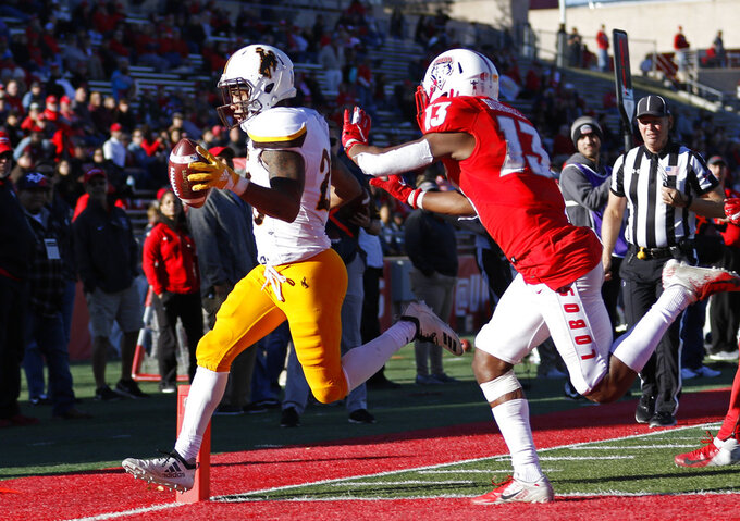 Wyoming wide receiver Austin Conway, left, scores a touchdown ahead of New Mexico cornerback Jalin Burrell (13) during the second half of an NCAA college football game in Albuquerque, N.M., Saturday, Nov. 24, 2018. Wyoming won 31-3. (AP Photo/Andres Leighton)