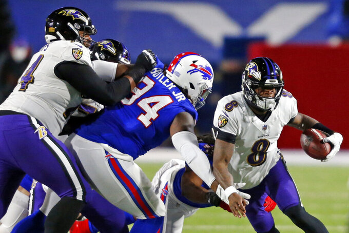 Baltimore Ravens quarterback Lamar Jackson (8) rushes past Buffalo Bills' Vernon Butler (94) during the first half of an NFL divisional round football game against the Baltimore Ravens Saturday, Jan. 16, 2021, in Orchard Park, N.Y. (AP Photo/Jeffrey T. Barnes)