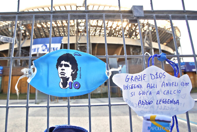 """A sign with writing reading in Italian """"Thank you god, teach the angels how to play soccer, farewell legend"""" is seen next to a face mask showing an icon of soccer legend Diego Maradona on the gates of the San Paolo stadium, in Naples, southern Italy, Thursday, Nov. 26, 2020. Maradona died Wednesday, Nov. 25, 2020 in Buenos Aires. (AP Photo/Alessandra Tarantino)"""
