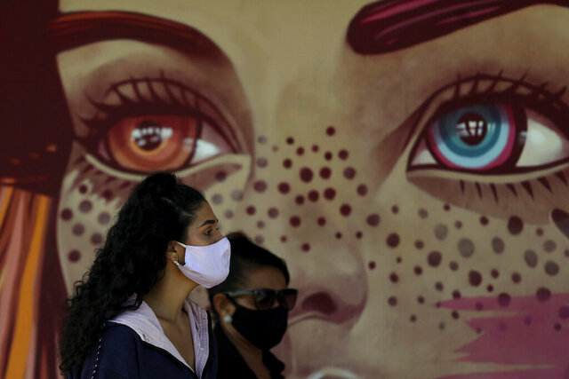 Women wear face masks amid the new coronavirus pandemic as they wait for a quick test at a COVID-19 testing site set up on a public school's basketball court in the Estrutural neighborhood of Brasilia, Brazil, Tuesday, May 26, 2020. According to officials, the objective is to expand surveillance and the tracking of possible asymptomatic positive cases, especially in poor, remote areas. (AP Photo/Eraldo Peres)