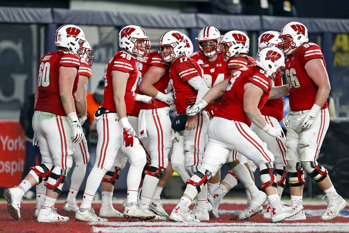 Wisconsin quarterback Jack Coan (17) celebrates with teammates after scoring a touchdown against Miami during the second half of the Pinstripe Bowl NCAA college football game Thursday, Dec. 27, 2018, in New York. Wisconsin defeated Miami 35-3. (AP Photo/Adam Hunger)