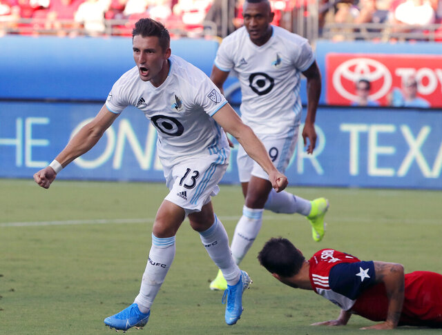 FILE - In this Aug. 10, 2019, file photo, Minnesota United's Ethan Finlay (13) and Angelo Rodriguez, rear left, celebrate Finlay's goal against FC Dallas in the first half of an MLS soccer match in Frisco, Texas. Major League Soccer and its players' union reached an agreement that paves the way for a summer tournament in Florida after the season was suspended by the coronavirus pandemic. The deal was announced by the Major League Soccer Players Association early Wednesday, June 3, 2020, following tense talks that led to some players skipping voluntary workouts and the league threatening a lockout. (AP Photo/Tony Gutierrez, File)