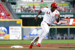 Cincinnati Reds' Aristides Aquino runs home to score on a single by Tucker Barnhart off Milwaukee Brewers starting pitcher Adrian Houser during the first inning of a baseball game Tuesday, Sept. 24, 2019, in Cincinnati. (AP Photo/John Minchillo)