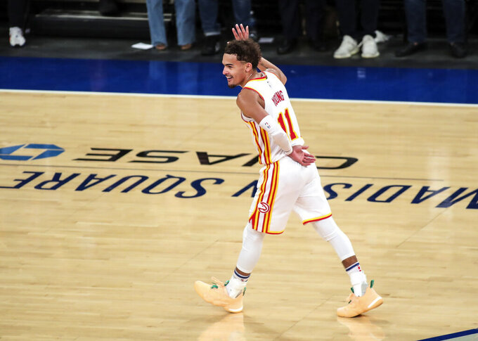 """FILE - In this June 2, 2021, file photo, Atlanta Hawks guard Trae Young waves to the crowd after making a 3-point shot against the New York Knicks in the fourth quarter of Game 5 of an NBA basketball first-round playoff series in New York. Young made a surprise appearance at """"WWE Friday Night SmackDown,"""" returning to the arena where he led the Hawks to an NBA playoff victory over the Knicks.Wearing a gray Hawks hoodie, Young was the perfect wrestling villain. (Wendell Cruz/Pool Photo via AP, File)"""