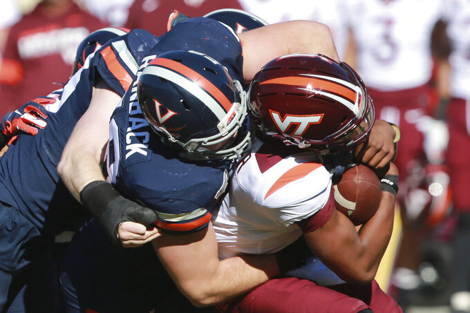 Virginia Tech quarterback Hendon Hooker, right, is wrapped up by Virginia defensive tackle Eli Hanback (58) during the first half of an NCAA college football game in Charlottesville, Va., Friday, Nov. 29, 2019. (AP Photo/Steve Helber)