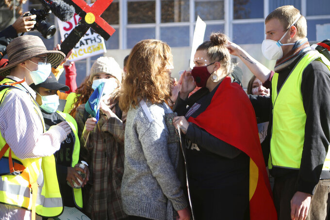 Protesters face off after one protester, center, interrupted a speech during a rally in Canberra, Australia, on Friday, June 5, 2010, prompted by the death of George Floyd, who died after being restrained by Minneapolis police officers on May 25. Thousands gathered in Australia's capital to remind Australians that the racial inequality underscored by Floyd's death was not unique to the United States. (AP Photo/Rod McGuirk)