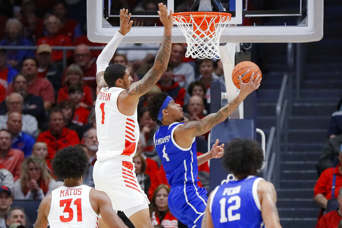 Drake's Anthony Murphy (4) shoots against Dayton's Obi Toppin (1) during the first half of an NCAA college basketball game, Saturday, Dec. 14, 2019, in Dayton, Ohio. (AP Photo/John Minchillo)
