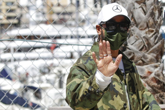 Mercedes driver Lewis Hamilton of Britain waves to supporters as he walks in the paddock at the Monaco racetrack, in Monaco, Wednesday, May 19, 2021. The Formula one race will be held on Sunday. (AP Photo/Luca Bruno)