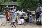 In this Thursday, June 18, 2020, photo, Alegba Jahyile, left, leader of Alegba and Friends, a Haitian roots/jazz band, and saxophonist Mark Kraszewski, second from left, play a set with other musicians in a free nightly concert at Brooklyn's Prospect Park boathouse in New York. From left are Jahyile, Kraszewski, percussionists Alix Julien and John Czolacz, and Lamarre Junior on bass. (AP Photo/Kathy Willens)