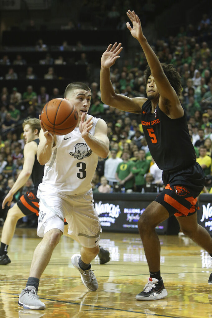 Oregon's Payton Pritchard, left, moves the ball under pressure form Oregon State's Ethan Thompson during the first half of an NCAA college basketball game in Eugene, Ore., Thursday, Feb. 27, 2020. (AP Photo/Chris Pietsch)