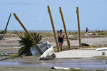 Pam Venissat, whose camp was destroyed by Hurricane Laura, takes a photo of the devastation in Holly Beach, La., Saturday, Aug. 29, 2020. (AP Photo/Gerald Herbert)